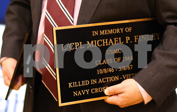 Kyle Bursaw – kbursaw@shawmedia.com<br /> <br /> Jay Brickman, principal at Hinckley-Big Rock High School, holds plaques for Michael P. Finley and Emil Viitaten on Monday at the end of a presentation honoring the two veterans, who died in the line of duty.<br /> <br /> Monday, Dec. 5, 2011.