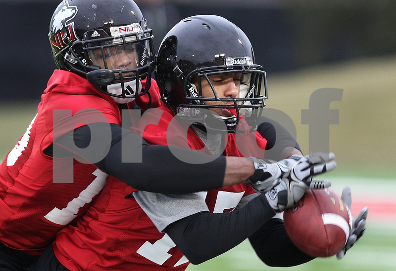 Kyle Bursaw – kbursaw@daily-chronicle.com<br /> <br /> Demetrius Stone (19, left) and Marckie Hayes (17, right) do a drill on breaking up catches during practice at Huskie Stadium on Tuesday, March 22, 2011.
