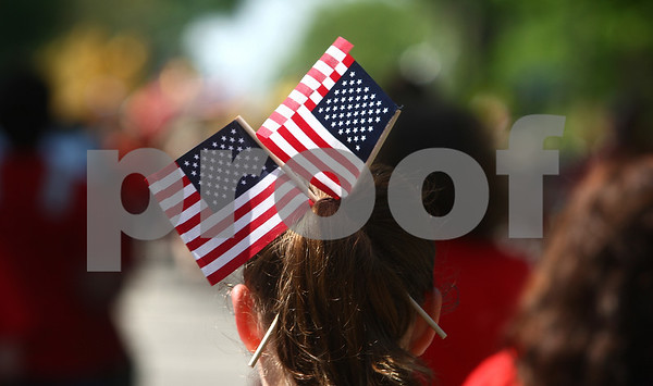 Kyle Bursaw – kbursaw@daily-chronicle.com<br /> <br /> A girl marching in the Memorial Day parade in Sycamore wears a pair of flags in her hair on Monday, May 30, 2011.