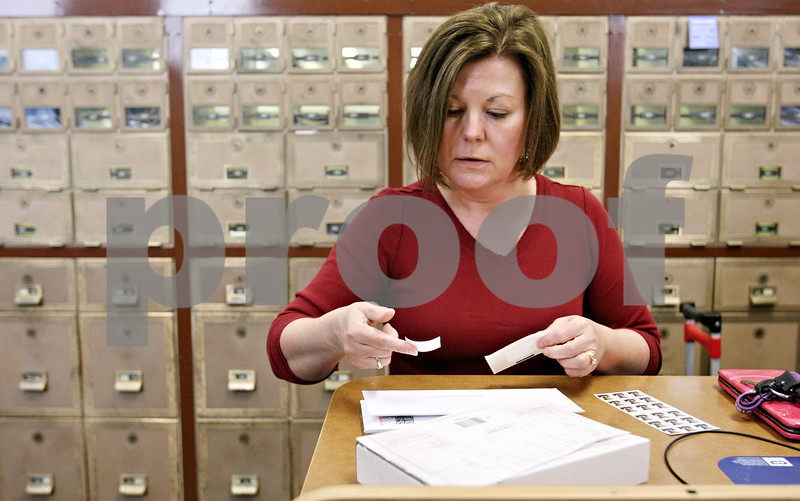 Rob Winner – rwinner@daily-chronicle.com<br /> <br /> During her lunch break, Pam Flora, of DeKalb, stops by the DeKalb post office on Monday afternoon to purchase stamps and to mail her tax forms.