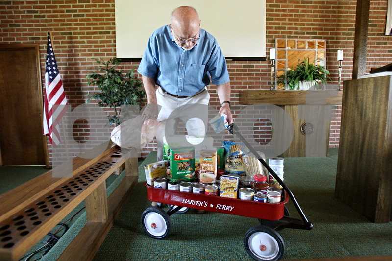 Rob Winner – rwinner@daily-chronicle.com<br /> <br /> On Tuesday afternoon at Grace Fellowship Church in Maple Park, Pastor James Harper, Jr. sets grocery items into a red wagon. Church members bring groceries and gift cards to fill the wagon and the pastor gives the donated goods to someone in need.