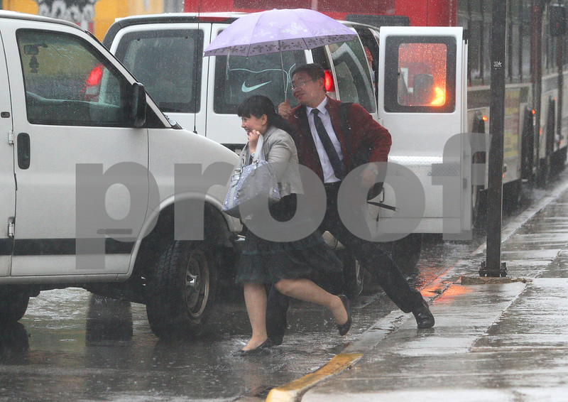 Kyle Bursaw – kbursaw@daily-chronicle.com<br /> <br /> Two people rush into a van, trying to avoid the rain outside the Holmes Student Center at Northern Illinois University in DeKalb, Ill. on Friday, May 13, 2011.