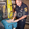 Kate Schott – kschott@shawmedia.com<br /> <br /> DeKalb County Sheriff's Chief Deputy Gary Dumdie takes out a case of deep sea fishing equpiment that will be available at a sheriff's auction planned for Saturday. The equipment was confiscated during an investgiation.