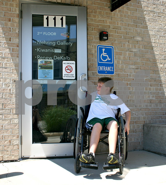 Kyle Hess, 11, struggles to open the handicap-accessible door at the DeKalb Chamber of Commerce building in downtown DeKalb Tuesday afternoon. Kyle, who's in the KEYS Leaders in Training program, was one of 11 participants who experienced what it was like getting around the downtown area with a physical impairment.<br /> <br /> By NICOLE WESKERNA - nweskerna@daily-chronicle.com