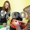 Rob Winner – rwinner@daily-chronicle.com<br /> <br /> April Panknin (from left to right) and Victoria Torres, 9, look over the nutrition facts on a can of soda pop, while Jada Edwards looks at a box of brownies on Monday afternoon in DeKalb. Panknin is offering a spring break camp that is helping children learn about nutrition, physical fitness and spiritual health.