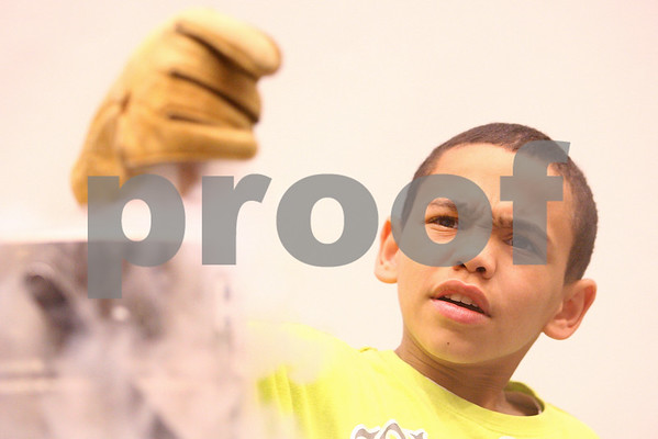 Kyle Bursaw – kbursaw@daily-chronicle.com<br /> <br /> Elon Scruggs, a 14-year-old from Rockford, reacts as he stirs some liquid nitrogen other ingredients to make ice cream during a week long STEM outreach in Faraday Hall at NIU in DeKalb, Ill. on Friday, July 1, 2011.