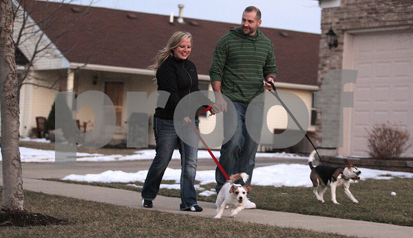 Kyle Bursaw – kbursaw@daily-chronicle.com<br /> <br /> Kyla Rader and Brent Hueber walk their dogs Marley (left) and Kody (right) after Hueber gets home from work on Tuesday, March 1, 2011 in their Sycamore neighborhood. The couple plan to tie the knot in July.