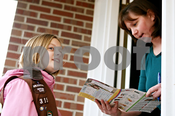 Rob Winner – rwinner@daily-chronicle.com<br /> <br /> Katie Steponaitis, 9, of Brownie Troop 355 sells an order of Girl Scout cookies to Sycamore resident Robin Slider on Monday afternoon.