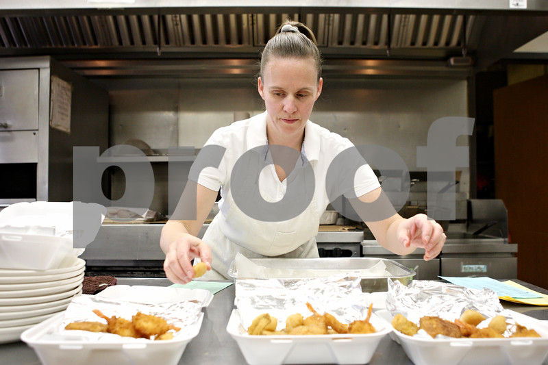 Rob Winner – rwinner@daily-chronicle.com<br /> <br /> Kathy Mohr prepares fried fish dinners at the Knights of Columbus Council 717 on Friday night in DeKalb.