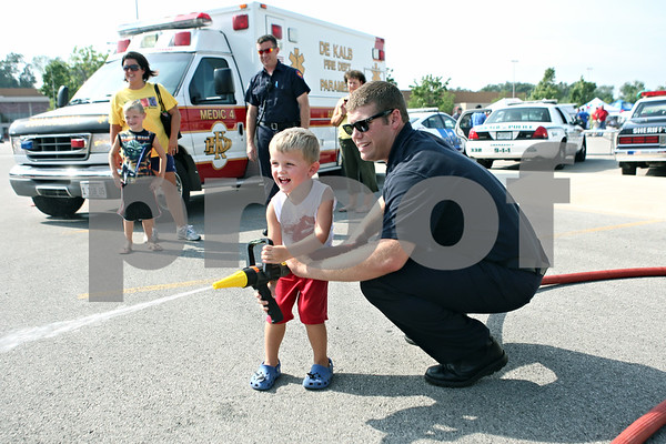 Rob Winner – rwinner@daily-chronicle.com<br /> <br /> DeKalb resident Evan Johnson, 3, sprays a fire hose with help from Noah Millard, of the DeKalb Fire Department, during National Night Out in the Target parking lot in DeKalb on Monday night.