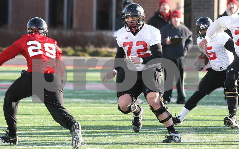 Kyle Bursaw – kbursaw@daily-chronicle.com<br /> <br /> Joe Pawlak (72) moves out to block Jordan Delegal (29) during practice at Huskie Stadium on Thursday, March 24, 2011.