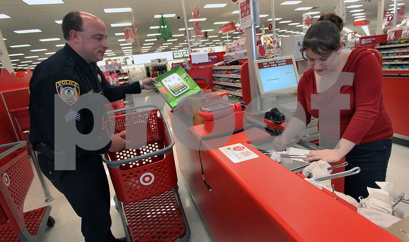 Wendy Kemp - For The Daily Chronicle<br /> Sgt. Jason Leverton checks out his toy selection with Target employee Rebecca Ruedin during the Shop with a Cop event at Target on Sunday.<br /> DeKalb 12/11/11