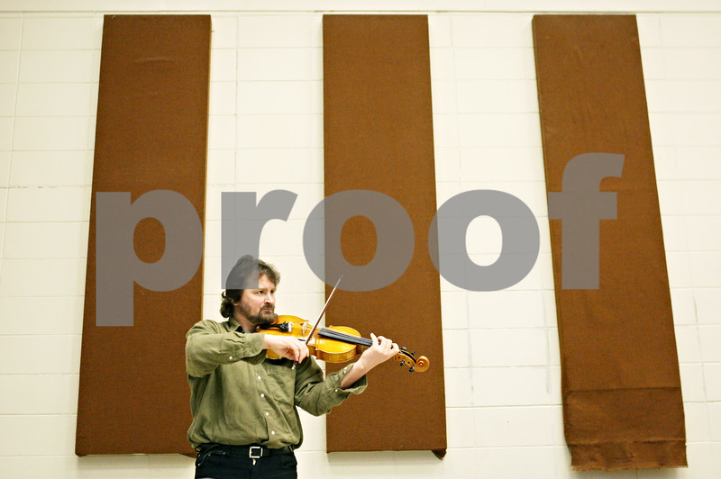 """Rob Winner – rwinner@daily-chronicle.com<br /> <br /> Yuri Orlov practices with his viola before the Kishwaukee Symphony Orchestra rehearsal at Northern Illinois University in DeKalb on Monday night. The orchestra is performing its last concert of the 2010-11 season, featuring the """"Titan"""" and """"Jupiter"""" symphonies on April 30."""