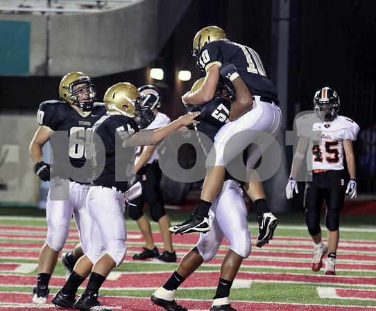 Wendy Kemp - For The Daily Chronicle<br /> Teammates congratulate Sycamore's Jordan Kalk (10) after he scored the first touchdown of Friday's game against DeKalb at Huskie Stadium.<br /> DeKalb 9/9/11