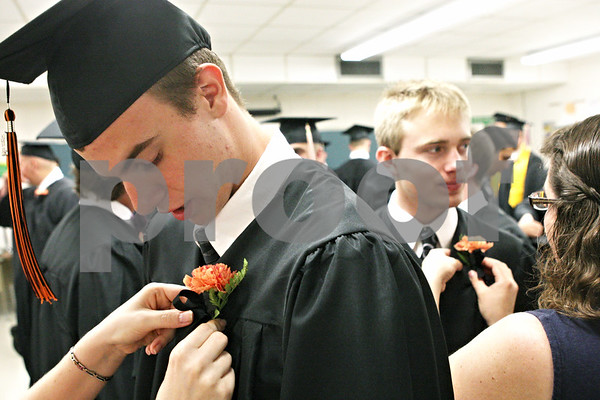 Rob Winner – rwinner@daily-chronicle.com<br /> <br /> Jared Kaelin (left) and Drew Baxter have flowers pinned to their gowns before the start of the Sandwich Community High School commencement ceremony on Sunday in Sandwich.