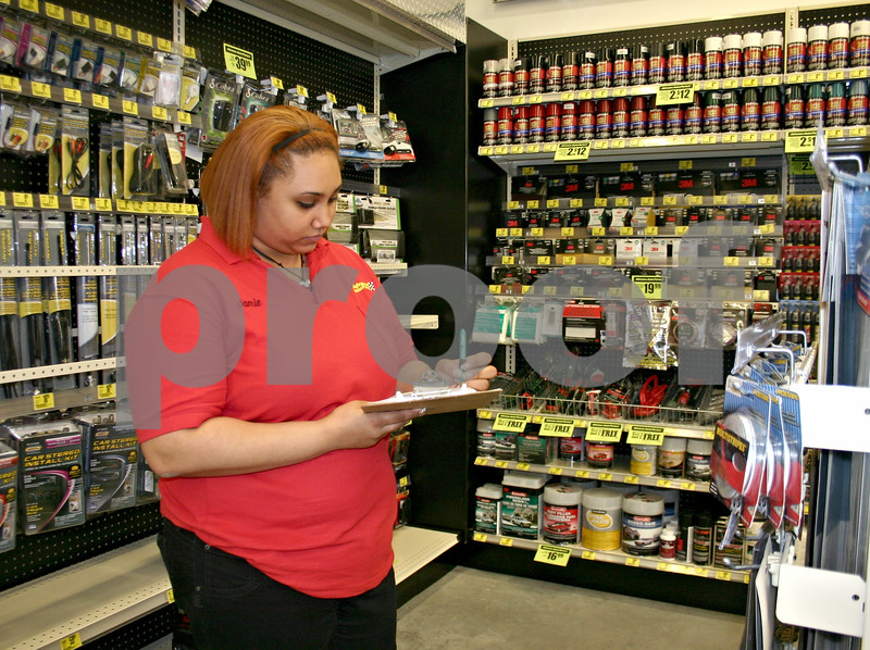 Jamie Aeschliman, salesperson at Advance Auto Parts in DeKalb, takes inventory of car bumper stickers at the store Thursday afternoon. Construction for the new Advance Auto Parts store began last fall and just opened last week.<br /> <br /> By NICOLE WESKERNA - nweskerna@daily-chronicle.com