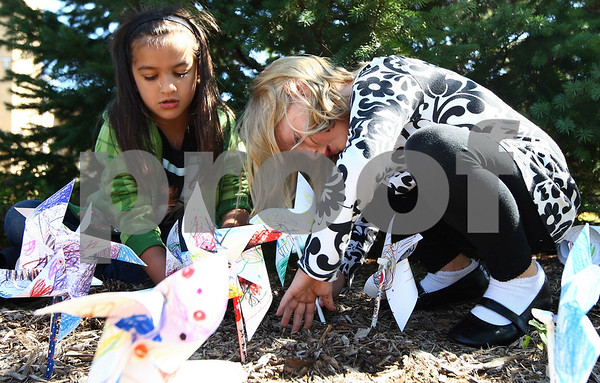 Kyle Bursaw – kbursaw@shawmedia.com<br /> <br /> Zoey Garcia (left) and Camryn Whitaker, both Sycamore West Elementary first-graders, plant their pinwheels in front of the school for a 'Pinwheels for Peace' project in Sycamore, Ill. on Wednesday, Sept. 21, 2011.