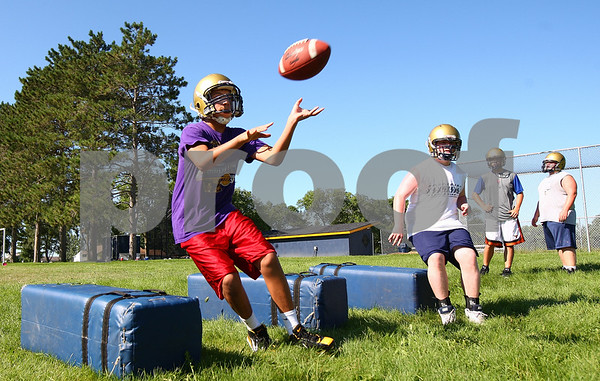 Kyle Bursaw – kbursaw@daily-chronicle.com<br /> <br /> Alex Flores catches a ball while navigating obstacles at Hiawatha's morning football practice on Thursday, Aug. 11, 2011.