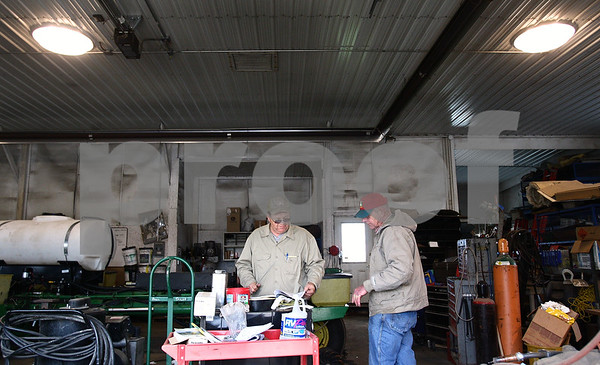 Kyle Bursaw – kbursaw@daily-chronicle.com<br /> <br /> Farmers Paul Taylor (left) and Paul Schweitzer talk while doing some maintenance on farm equipment inside because the weather was too wet and cold to start planting on Wednesday, April 27, 2011 in Esmond, Ill.