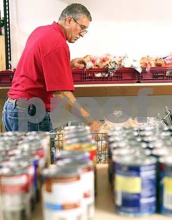 Kyle Bursaw – kbursaw@daily-chronicle.com<br /> <br /> Gary Billings, the Salvation Army Food Pantry coordinator, restocks the bread before clients come in on Thursday morning in DeKalb, Ill.