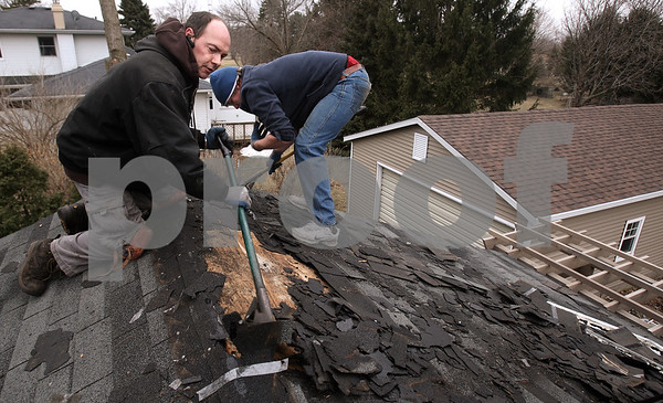 Kyle Bursaw – kbursaw@daily-chronicle.com<br /> <br /> Andrew Kellogg, owner of DeKalb Roofing, and his brother Jessie Thornton tear off the old roofing prior to installing new roofing at a residence in Cortland, Ill. on Thursday, March 10, 2011.