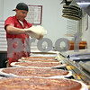 Chris Schneider, general manager of Toppers Pizza in DeKalb, practices for a pizza-making competition coming up later this month while his co-worker times him. <br /> <br /> By NICOLE WESKERNA - nweskerna@daily-chronicle.com