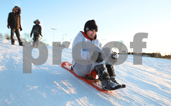 Kyle Bursaw – kbursaw@daily-chronicle.com<br /> <br /> Zaria Johnson, 14, slides down a hill on a snowboard as family members Nathan Hanson (left) and Ania Johnson look on. The trio was sliding for about half an hour at Hopkins Park in DeKalb, Ill. on Thursday, Feb. 3, 2011.