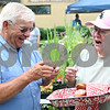 Rob Winner – rwinner@daily-chronicle.com<br /> <br /> Vernon Carey, of Kingston, purchases a pastry from Dolly Bruder in the open air market during the Summer Farm Fest in downtown Genoa on Saturday morning. Bruder was selling the pastries to benefit St. Catherine of Genoa Knights of Columbus.