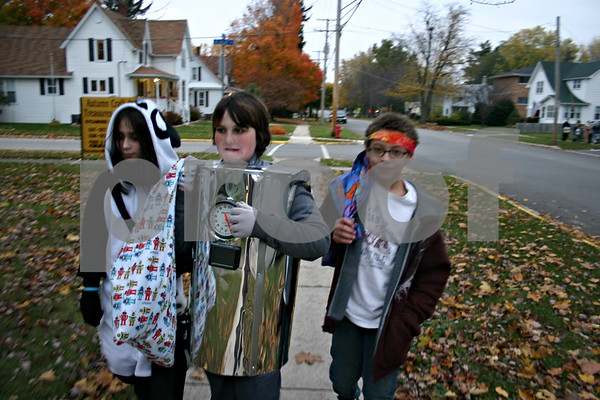 "Jeff Engelhardt – Sam Cottone (left), Ben Cottone (middle) and Keanan Uebel (right) carry their pillow cases of candy to the next house as they trick-or-treat Monday in Sycamore. The Cottone's house is one of the most festive in the neighborhood as it features a ""Dead End Cemetery"" display."