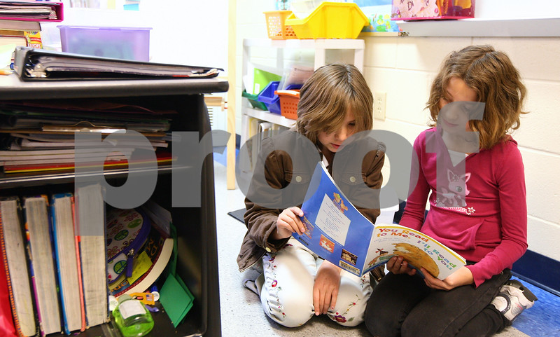 Kyle Bursaw – kbursaw@shawmedia.com<br /> <br /> Kaylee Meyer and Cassidy Sunleaf, fifth-graders at Genoa Elementary, read 'You Read to Me, I'll Read to You' aloud during a designated reading time in Mrs. Hill's class on Friday, Oct. 28, 2011.
