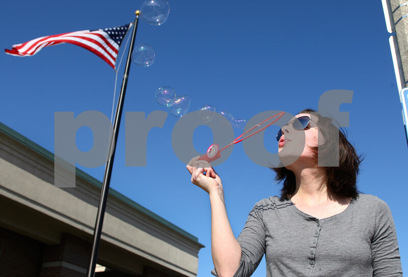 Kyle Bursaw – kbursaw@daily-chronicle.com<br /> <br /> Northern Illinois student Shannon Reimann blows bubbles with friend Michael Sunderman (not pictured) while waiting for the bus on Lincoln Highway in DeKalb, Ill. on Friday, April 30, 2011.