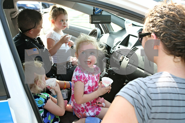 Rob Winner – rwinner@daily-chronicle.com<br /> <br /> 2-year-old Rori Cottrell (second from right) sits on her twin sister's lap, Rhiannon, from within a Northern Illinois University police car while their family attended National Night Out in the Target parking lot in DeKalb on Monday night.