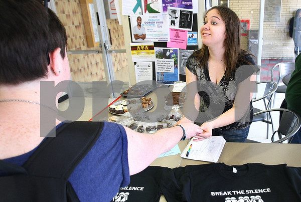 Kyle Bursaw – kbursaw@daily-chronicle.com<br /> <br /> PRISM member Lauren Pagan (right) accepts an NIU student's money who bought a t-shirt during their celebration of PRISM's 41st anniversary at NIU on Wednesday, April 13, 2011. The t-shirts were for a Day of Silence on Friday, April 15, 2011.