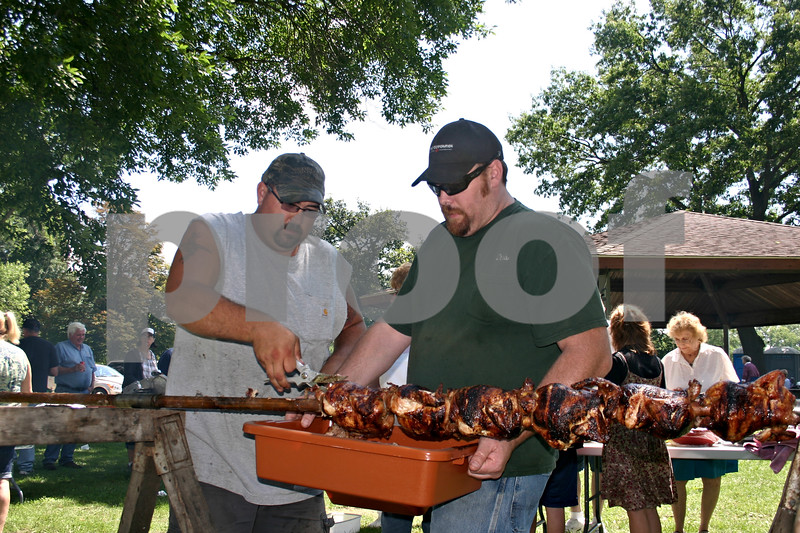 Ben Drake (left) and Chris Barber, both of Sycamore, remove chickens from the rotisserie at the Sycamore Veterans Memorial Home picnic Sunday at Sycamore Community Park. Organizers said the annual picnic is an opportunity to honor veterans and their families.