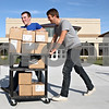 Rob Winner – rwinner@shawmedia.com<br /> <br /> Daniel Engstrom (left) and fellow senior Hayden Perkins wheel in boxes filled with books from the DeKalb Public Library into DeKalb High School on Thursday, Sept. 15, 2011. The books are part of the Big Read program of the National Endowment for the Arts to promote literacy throughout the country.