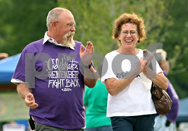 Rob Winner – rwinner@daily-chronicle.com<br /> <br /> Cancer survivor Brad Grimes (left) and his wife Doris Grimes, of Genoa, walk with participants of the Relay for Life of DeKalb County event on Friday evening in Sycamore. Brad is a four year survivor.