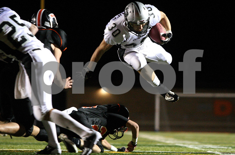 Kyle Bursaw – kbursaw@shawmedia.com<br /> <br /> Kaneland running back Jesse Balluff hurdles over a DeKalb defensive back Jake Young in the first quarter of the game in DeKalb, Ill. on Friday, Sept. 30, 2011.
