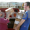 Rob Winner – rwinner@shawmedia.com<br /> <br /> Edith Craig (left) of the DeKalb Public Library hands Daniel Engstrom a stack of boxes filled with books outside DeKalb High School on Thursday, Sept. 15, 2011. The books are part of The Big Read program of the National Endowment for the Arts to promote literacy throughout the country.