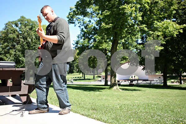 """Rob Winner – rwinner@shawmedia.com<br /> <br /> DeKalb resident David Thompson practices the guitar at Hopkins Park on Labor Day, Monday, Sept. 5, 2011. """"It's a really nice day and I wanted to play the guitar and I wanted to be outside so I came here,"""" said Thompson."""