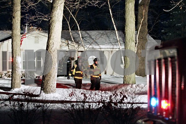 Rob Winner – rwinner@daily-chronicle.com<br /> <br /> Firefighters check a house fire on Ash Road in Genoa on Tuesday evening.