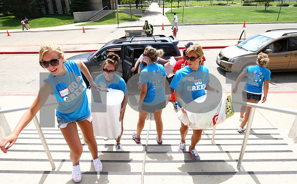 Kyle Bursaw – kbursaw@daily-chronicle.com<br /> <br /> Shelley Ryan (from left), Brittany Batavia and Thomasina Tarvis, all volunteers from Delta Zeta sorority, carry the belongings of students moving into Grant Hall up the stairs and into the lobby of the building on Thursday, Aug. 18, 2011. Further volunteers helped students bring their things into their rooms.