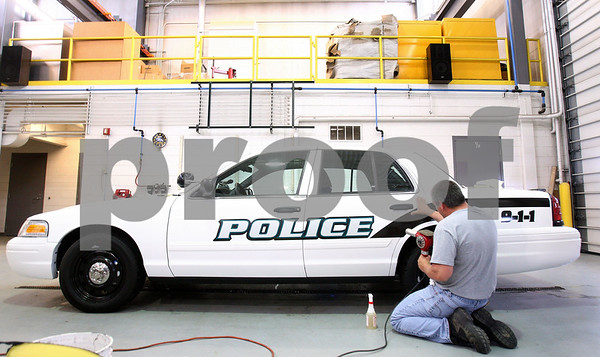 Kyle Bursaw – kbursaw@daily-chronicle.com<br /> <br /> Johnn Lucius, a sign technician for the city of DeKalb, applies heat and shapes a decal to the curve of the door handle on one of the new police squad cars on Wednesday, May 25, 2011.