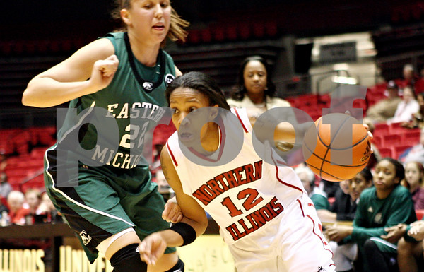 Rob Winner – rwinner@daily-chronicle.com<br /> <br /> Northern Illinois guard Danielle Pulliam (12) moves past Eastern Michigan guard Cassie Schrock (22) during the first half of their game in DeKalb, Ill. on Wednesday, Jan. 5, 2011.