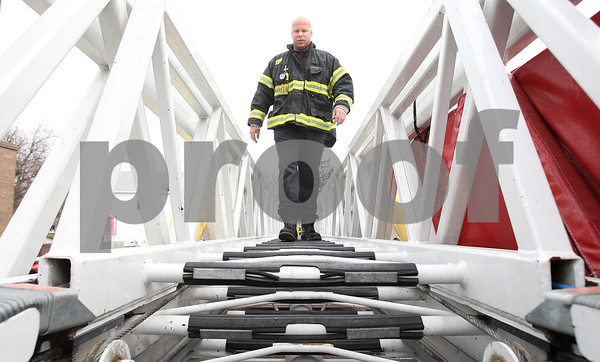 Kyle Bursaw – kbursaw@daily-chronicle.com<br /> <br /> DeKalb firefighter Jason Pavlak walks down ladder of the department's ladder truck, which is now more than 20 years old, during a maintenance check on Wednesday, April 6, 2011 at Station no. 1 in DeKalb, Ill.
