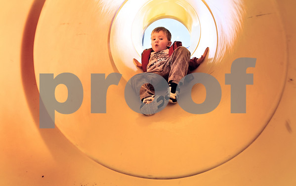 Kyle Bursaw – kbursaw@daily-chronicle.com<br /> <br /> Jeremy Clay, 3, glides his way down a slide at Lions Park in DeKalb, Ill. on Wednesday, March 16, 2011.