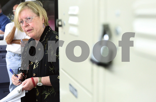 Kyle Bursaw – kbursaw@daily-chronicle.com<br /> <br /> Dee Coover, director of the DeKalb Public Library, takes notes by some lockers in an employee section of the building as Warren Graham, a consultant from North Carolina, addresses security risks on Thursday, Aug. 4, 2011.
