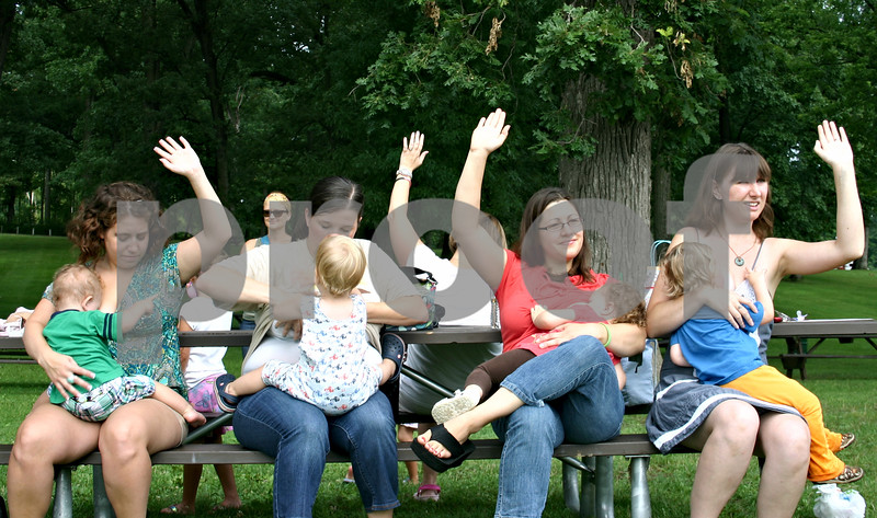 """By Nicole Weskerna - nweskerna@daily-chronicle.com<br /> <br /> Women participating in Saturday's """"big latch"""" at Hopkins Park in DeKalb raise their hands to be counted. Eight women participated in the breastfeeding event to kick off World Breastfeeding Week, and each breastfed their children for one minute in hopes of helping break the record for the largest number of women breastfeeding simultaneously."""
