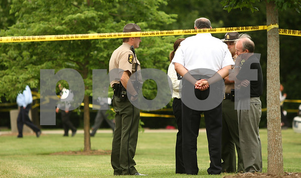 Kyle Bursaw – kbursaw@daily-chronicle.com<br /> <br /> Multiple law enforcement officials including Master Sergeant Isaiah Vega (back right) DeKalb County State's Attorney Clay Campbell (front right) and Sycamore Police Chief Don Thomas (center, facing away) talk behind police tape in Elmwood Cemetery after the exhumation of Maria Ridulph's body on the morning of Wednesday, July 27, 2011.