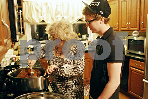 Rob Winner – rwinner@shawmedia.com<br /> <br /> Genoa resident Cindy Newman and her son, Billy Newman, 15, check the progress of their turkey before a Thanksgiving dinner with family and friends on Wednesday night. Cindy Newman and her son lost there home after a fire back in October.