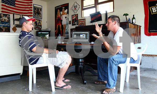 Kyle Bursaw – kbursaw@shawmedia.com<br /> <br /> Entrepreneurs Alex Broches,  (left) and Dwight Taylor  talk business details in Broches' garage in Sycamore, Ill. on Wednesday, Aug. 31, 2011. The two met through the other websites they run and are now partners in udidfast.com.